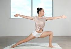 De jonge mooie vrouw die yoga doen stelt in ruimte Stock Foto