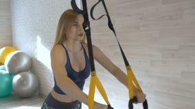 De jonge mooie vrouw doet oefeningen in een geschiktheidsruimte stock footage