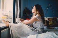De jonge mooie vrouw drinkt koffie thuis liggend op bed Royalty-vrije Stock Afbeelding