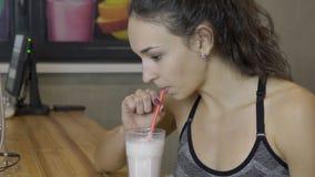 De jonge mooie vrouw drinkt milkshake in de bar in sportclub na de oefeningen stock footage