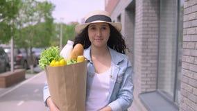 De jonge mooie vrouw in een een denimjasje en hoed draagt een pakket met producten die een goede stemming hebben en glimlacht 4K stock videobeelden