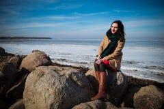 De jonge mooie vrouw in elegante kleren met sjaal zit op de kustlijn in wintertijd Royalty-vrije Stock Fotografie