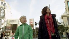 De jonge mooie vrouw en haar charmante zoon lopen op een straat in Las Vegas stock video