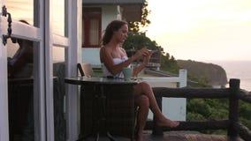 De jonge mooie vrouw gebruikt cellphone en het drinken koffie op terras tijdens zonsondergang in bergen met verbazende overzeese  stock footage