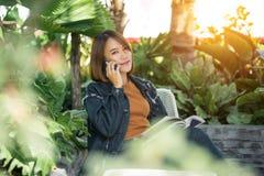 De jonge mooie vrouw gebruikt cellphone en luistert aan muziek stock afbeelding