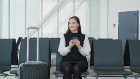 De jonge mooie vrouw gebruikt een smartphone terwijl het wachten op een trein als aankomst het aantrekkelijke jonge blondevrouw g stock video