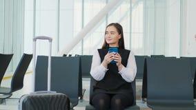 De jonge mooie vrouw gebruikt een smartphone terwijl het wachten op een trein als aankomst het aantrekkelijke jonge blondevrouw g stock videobeelden