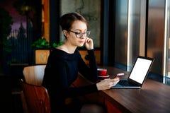 De jonge mooie vrouw in de glazenwerken aangaande laptop, gebruikt een smartphone, een freelancer, een computer, financieel anali royalty-vrije stock foto