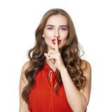 De jonge mooie vrouw heeft wijsvinger aan lippen als teken van sile gezet royalty-vrije stock foto