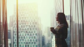 De jonge mooie vrouw het drinken koffie en bewondert mening thuis van venster tijdens zonsondergang 3840x2160 stock videobeelden