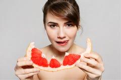 De jonge mooie vrouw of het leuke sexy meisje met lang haar houden de plak van het grapefruitfruit Royalty-vrije Stock Foto's