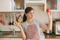 De jonge mooie vrouw kookt in de keuken royalty-vrije stock afbeelding