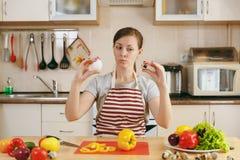 De jonge mooie vrouw kookt in de keuken royalty-vrije stock foto's