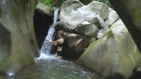 De jonge mooie vrouw in langzame motie zet haar handen onder de stroom van kleine waterval en kijkt aan camera in berg stock video