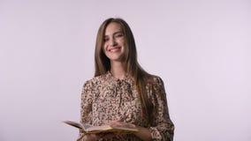 De jonge mooie vrouw leest boek, lettend op bij camera, het glimlachen, witte achtergrond stock footage
