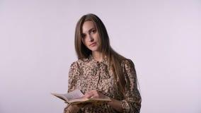 De jonge mooie vrouw leest boek, lettend op bij camera, witte achtergrond stock footage