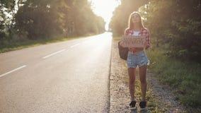 De jonge mooie vrouw lift die zich op de wegholding overal bevinden ondertekent Jonge volwassenen stock footage