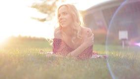 De jonge mooie vrouw ligt op het gras in het park stock videobeelden