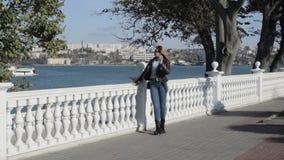 De jonge mooie vrouw loopt dichtbij overzees, promenade stock footage