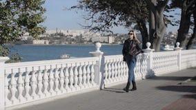 De jonge mooie vrouw loopt dichtbij overzees, promenade stock videobeelden