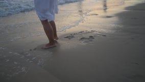 De jonge mooie vrouw loopt door het overzees bij zonsondergang Benenclose-up In een witte kleding en een witte hoed stock videobeelden