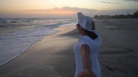 De jonge mooie vrouw loopt door het overzees bij zonsondergang In een witte kleding en een witte hoed Zij loopt vanaf de camera,  stock footage