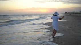 De jonge mooie vrouw loopt door het overzees bij zonsondergang In een witte kleding en een witte hoed De vrouw is zwanger Zij loo stock videobeelden