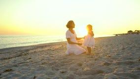 De jonge mooie vrouw loopt met haar weinig dochter op de kust bij zonsondergang Zij zijn gelukkig Silhouetten tegen stock video