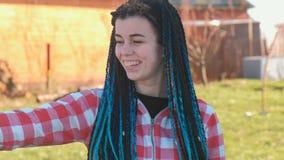 De jonge mooie vrouw met blauwe Afrikaanse vlechten kijkt rond en lacht, bekijkend de camera stock footage