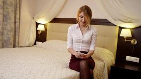 De jonge mooie vrouw met blond haar babbelt in telefoon stock footage