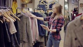 De jonge mooie vrouw met een tabletpc onderzoekt kleren op een rek in een kledingsopslag stock videobeelden
