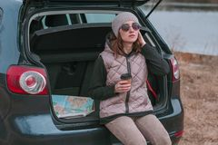 De jonge mooie vrouw met kop van koffie zit in open boomstam van auto en het letten op wegenkaart royalty-vrije stock foto's