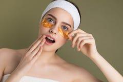 De jonge mooie vrouw met natuurlijk maakt omhoog het verwijderen van gouden flard van onder haar oog stock fotografie