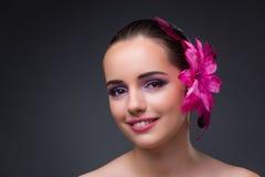De jonge mooie vrouw met orchideebloem stock fotografie