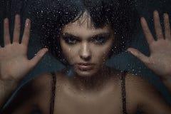 De jonge mooie vrouw met provocatief maakt omhooggaand en modieus loodjeskapsel zich bevindt achter het venster met regendalingen stock afbeelding