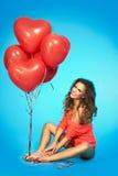 De jonge mooie vrouw met rood hart shpaed ballons Royalty-vrije Stock Foto's