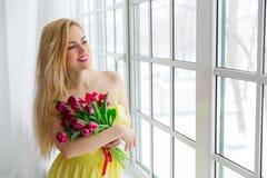 De jonge mooie vrouw met tulpenbos in gele kleding bekijkt venster Stock Fotografie