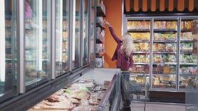 De jonge mooie vrouw neemt fles met iets smakelijk van hoogste plank dichtbij koelkast stock videobeelden