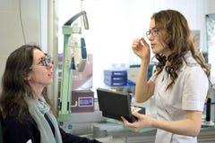 De jonge mooie vrouw ondergane procedure van de lensmontage in het uitstekende testende passende kader van de stijllens met oftal stock fotografie