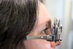 De jonge mooie vrouw ondergane procedure van de lensmontage in het uitstekende testende passende kader van de stijllens met oftal stock foto's