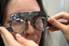 De jonge mooie vrouw ondergane procedure van de lensmontage in het uitstekende testende passende kader van de stijllens met oftal royalty-vrije stock foto