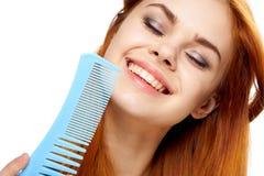 De jonge mooie vrouw op wit geïsoleerde achtergrond houdt een haarborstel, glimlach, portret Royalty-vrije Stock Fotografie