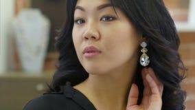 De jonge mooie vrouw past lippenstift voor spiegel en het glimlachen toe stock videobeelden