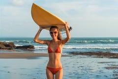 De jonge mooie vrouw in rode bikini en zonglazen houdt in handen een branding op het oceaanstrand bij zonsondergang royalty-vrije stock foto