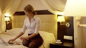 De jonge mooie vrouw schrijft iets in haar laptop en zit op het bed stock video