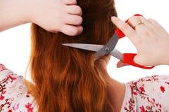 De jonge mooie vrouw snijdt rood haar Stock Afbeeldingen