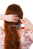 De jonge mooie vrouw snijdt rood lang haar Stock Fotografie