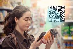 De jonge mooie vrouw tast het product in de supermarkt af Het concept moderne technologie licht stock foto