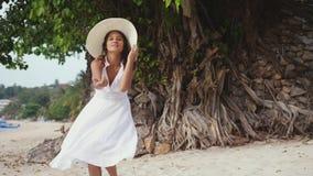 De jonge mooie vrouw in witte drees en een hoed kijkt het achter wenken voor zich op tropisch strand Langzame Motie 3840x2160 stock video