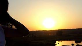 De jonge Mooie Vrouw zet Haar Haar in Orde en bekijkt Zonsondergang in slo-Mo stock videobeelden
